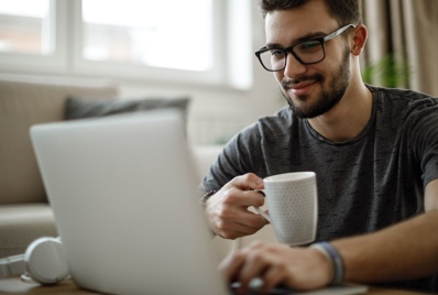 Man using a computer while drinking coffee